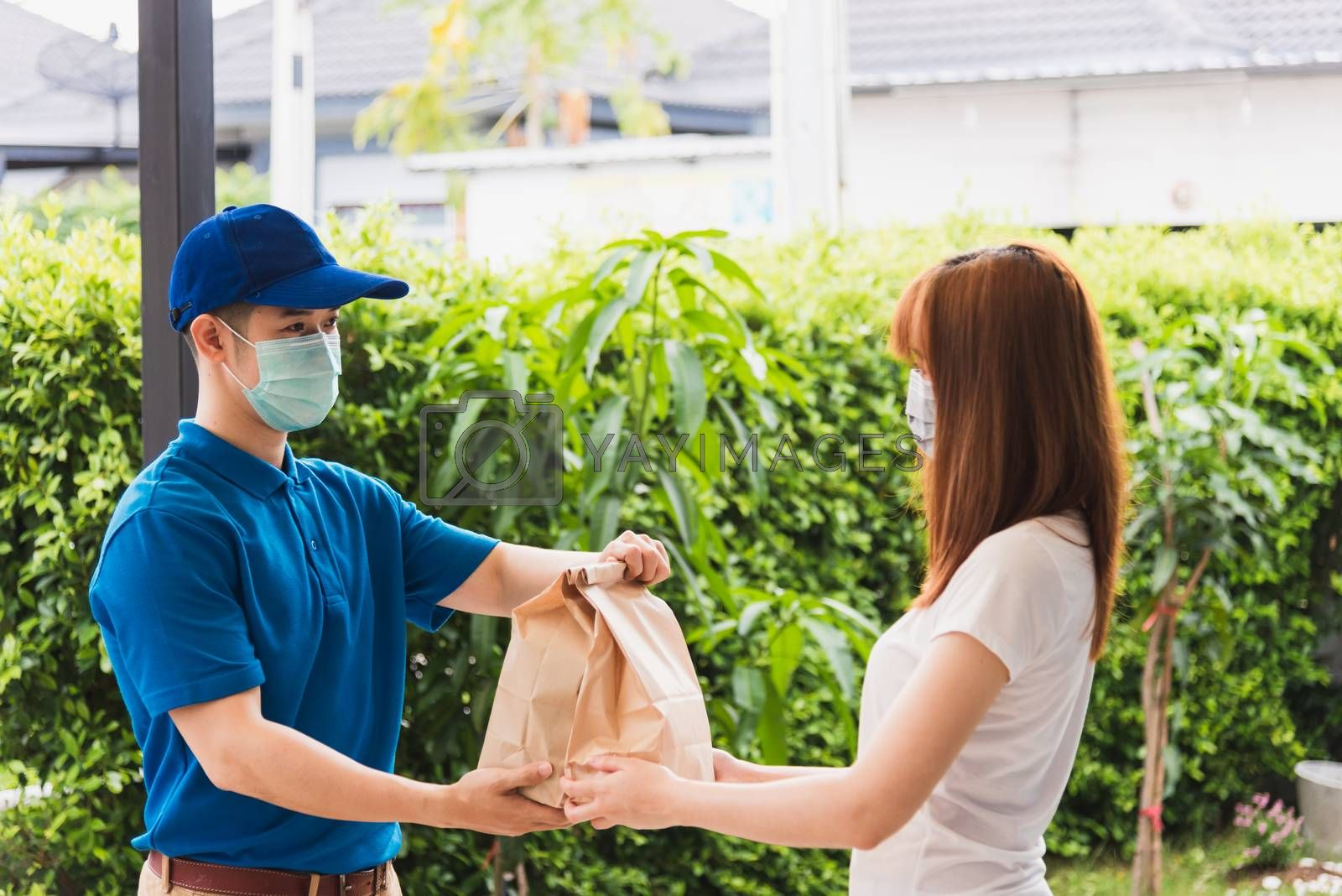 Asian delivery express courier young man giving paper bags fast food to woman customer receiving both protective face mask, under curfew quarantine pandemic coronavirus COVID-19