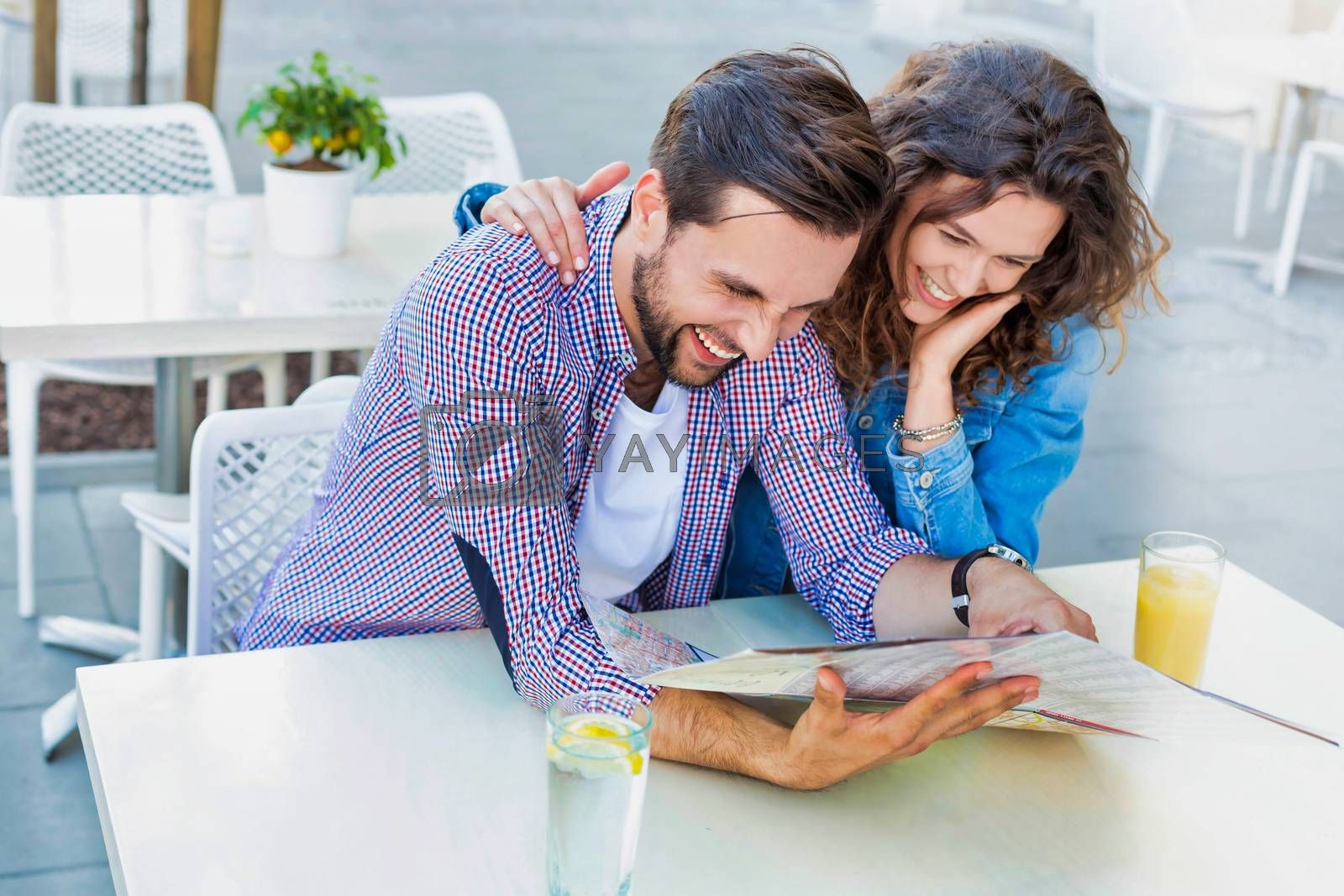 Portrait of young attractive couple looking on map while waiting for their food in restaurant