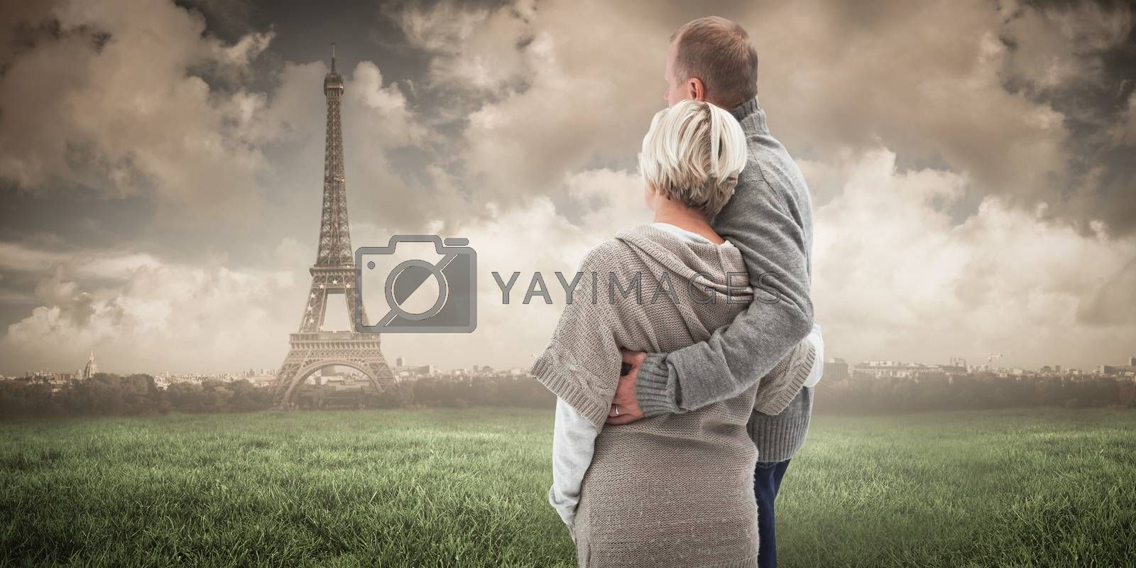 Happy mature couple in winter clothes against paris under cloudy sky