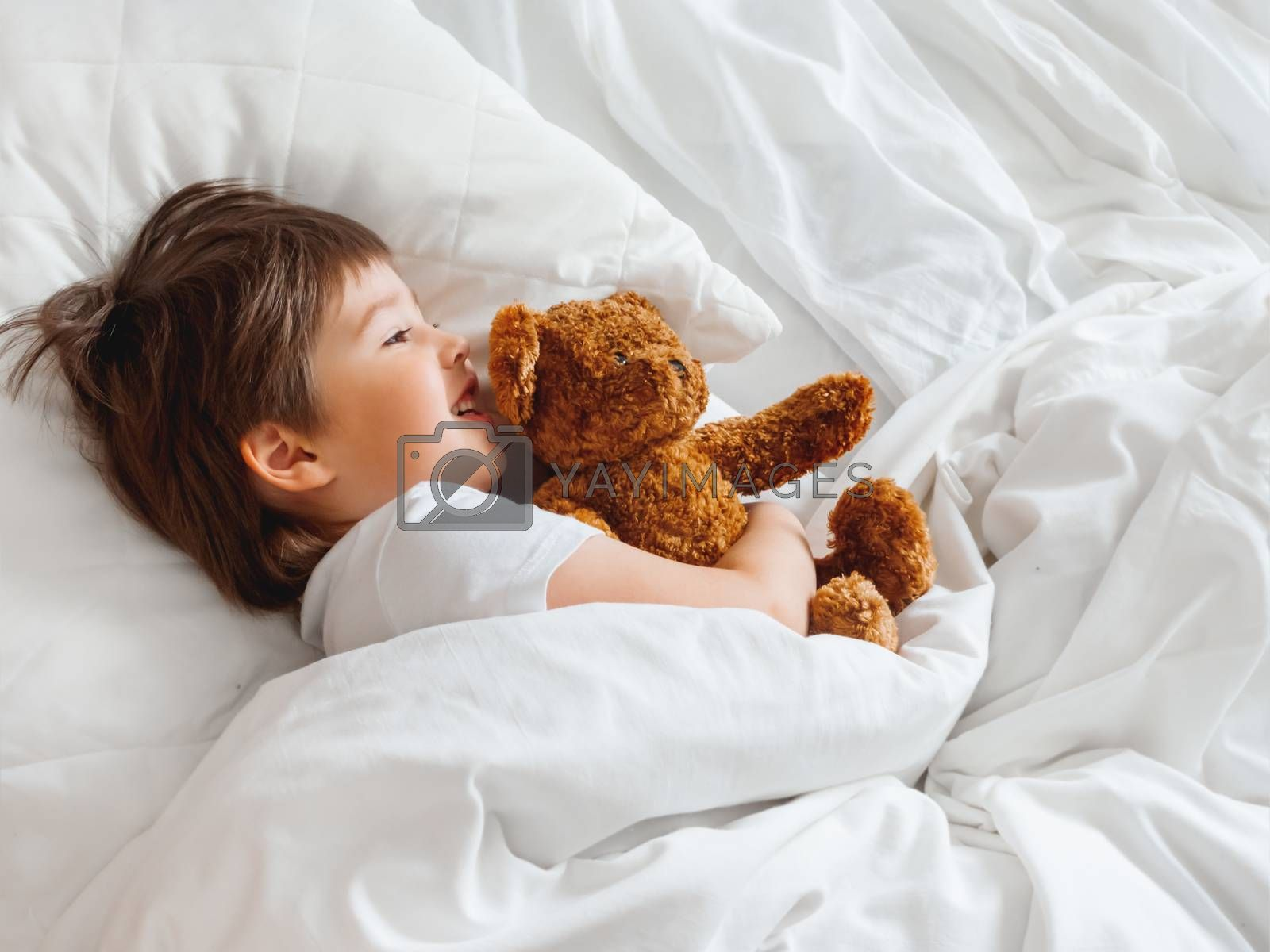 Toddler lies in bed with cute teddy bear. Little boy under white blanket with fluffy toy. Plush guard watches out child's sleep. Morning bedtime at cozy home.