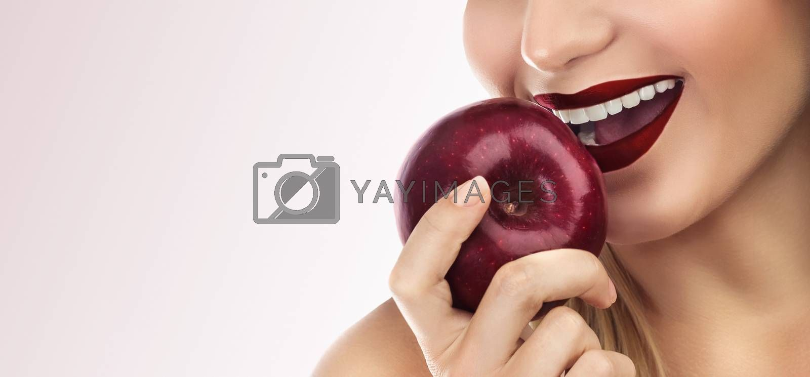 Closeup photo of a woman's face, lips with red lipstick, female biting  fresh red apple, isolated on a clean background, beautiful smile with perfect white teeth, dental care concept