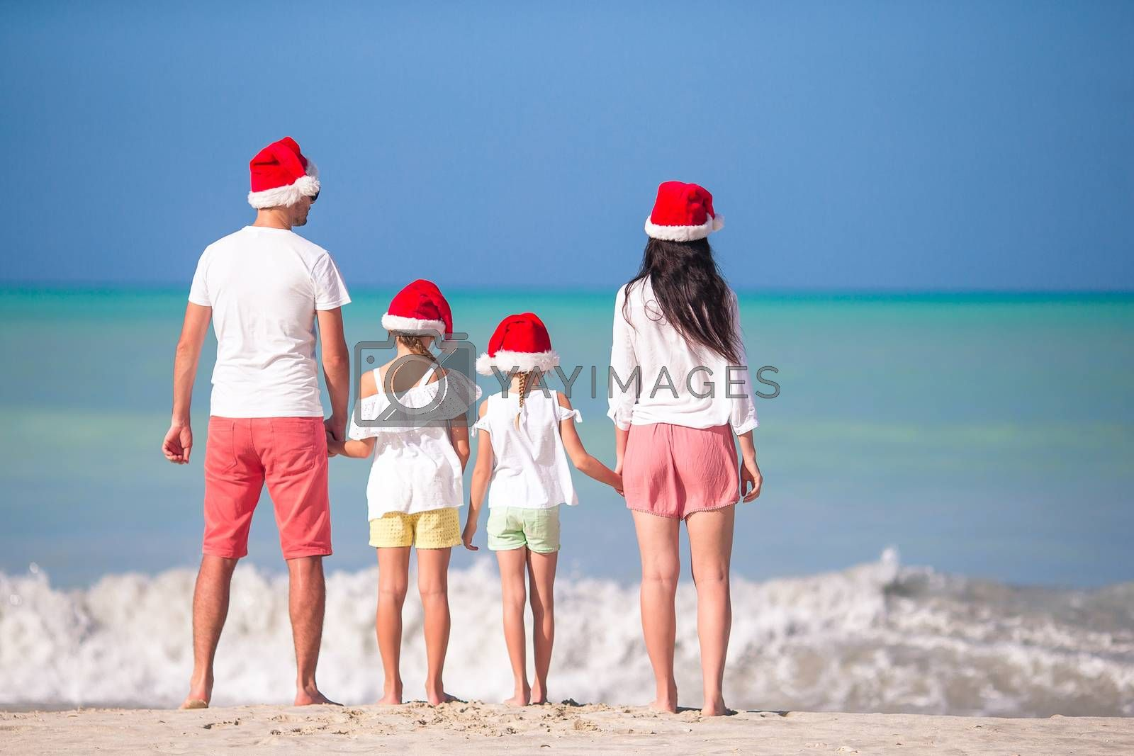 Happy family in Xmas hats on a tropical beach celebrating Christmas vacation