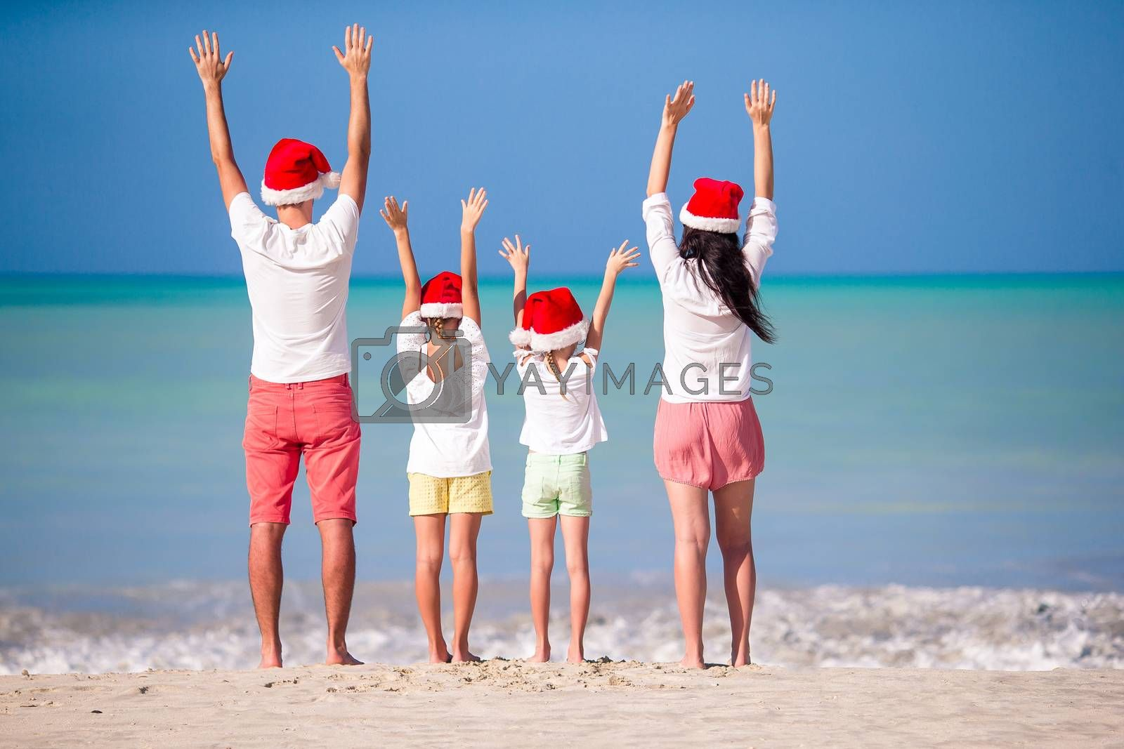 Happy family on a tropical beach celebrating Christmas vacation