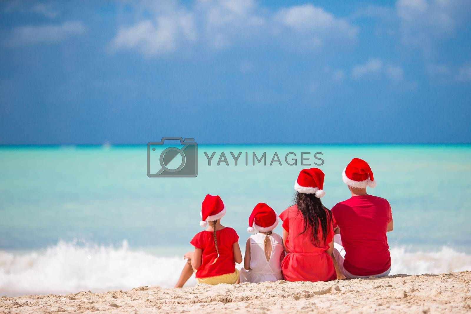 Happy family on a tropical beach celebrating Christmas vacation - Image