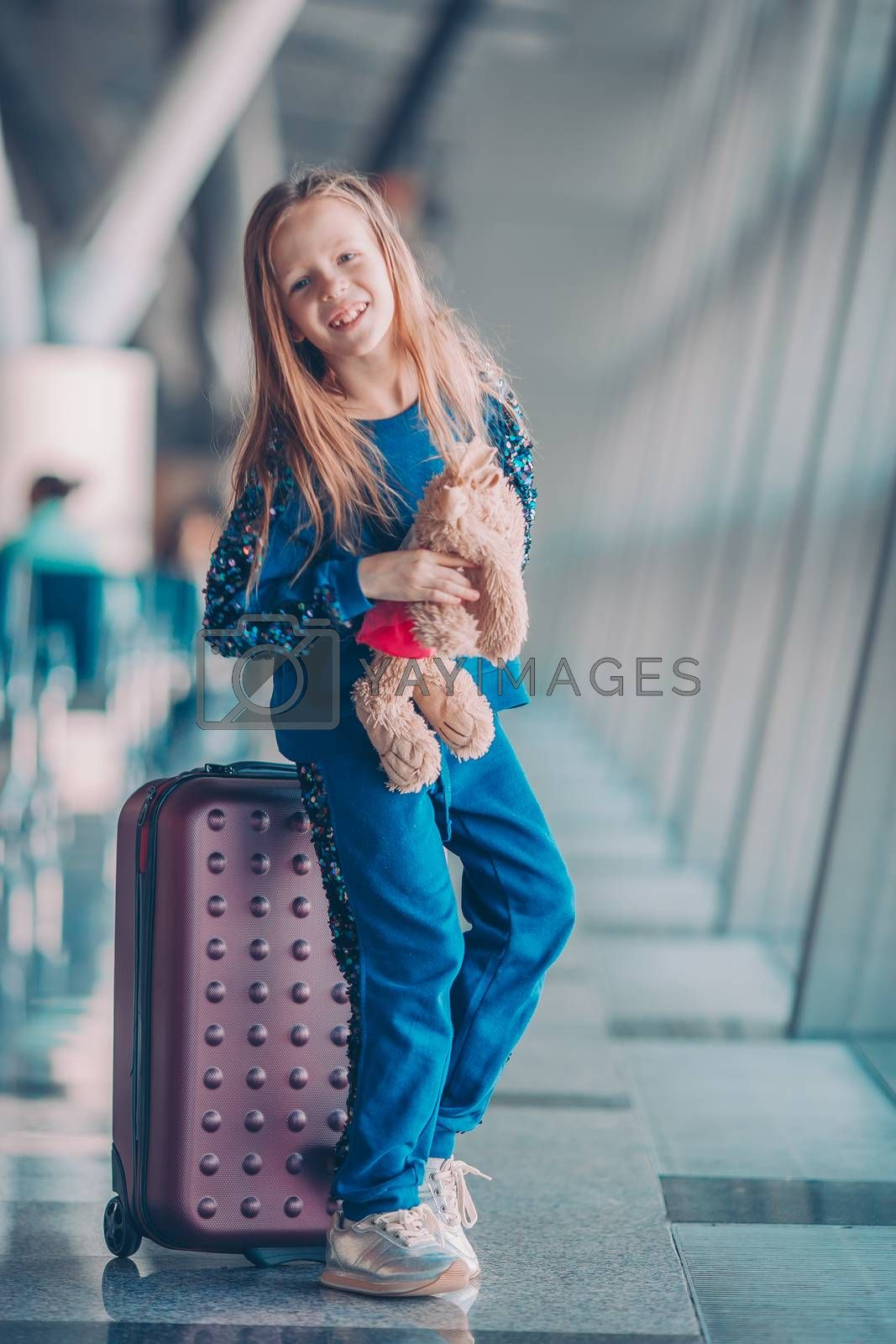 Little adorable kid in airport waiting for boarding indoors