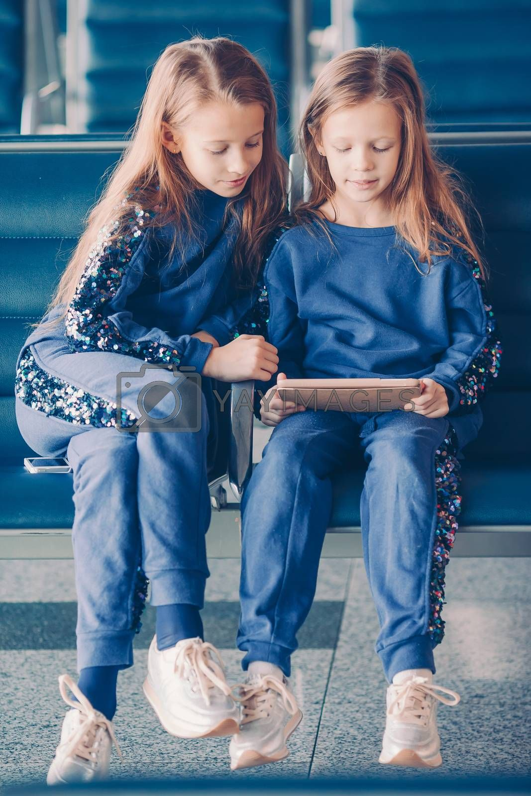 Little kids together in airport waiting for boarding. Two sisters playing by smartphone near big windows