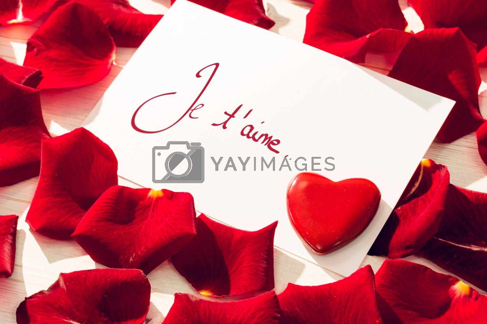 Valentines love hearts against card with red rose petals