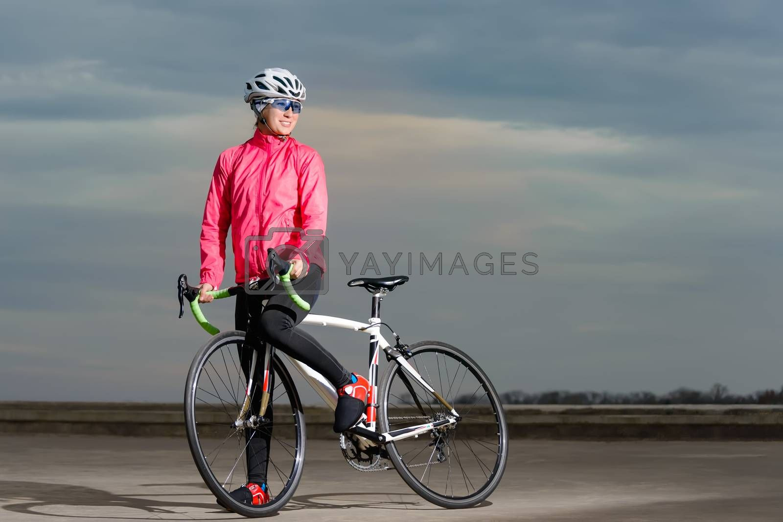 Portrait of Young Woman Cyclist with Road Bike at Sunset. Healthy Lifestyle and Outdoor Sport Concept.