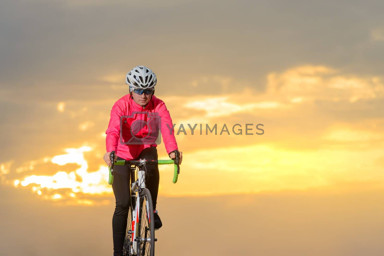 Young Woman Cyclist Riding Road Bike at Sunset. Healthy Lifestyle and Outdoor Sport Concept.
