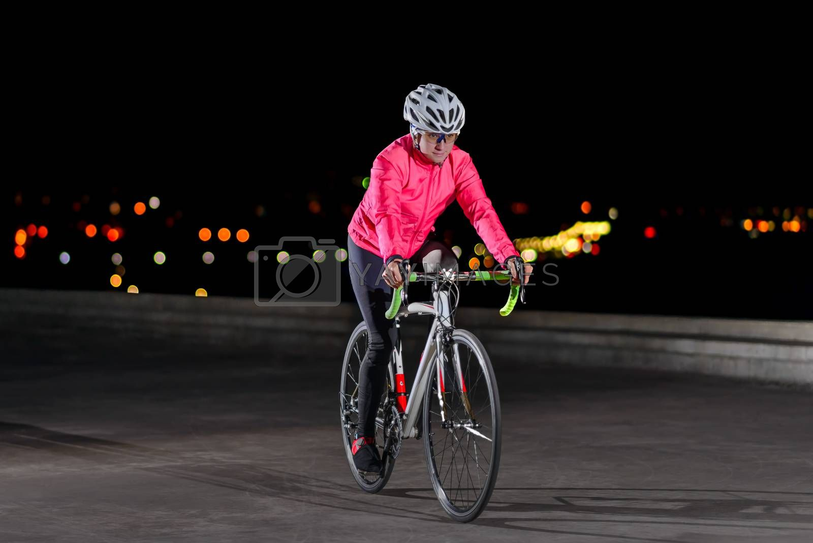 Young Woman Cyclist Riding Road Bike. Night City Lights at the Background. Healthy Lifestyle and Urban Sport Concept.