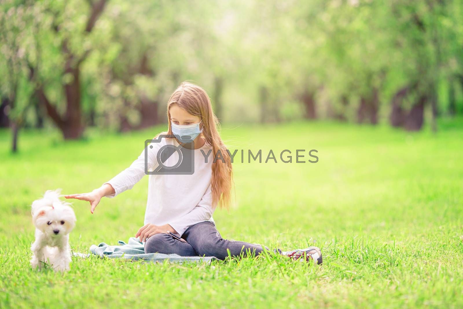Little girl with dog wearing protective medical mask for prevent virus outdoors in the park by travnikovstudio