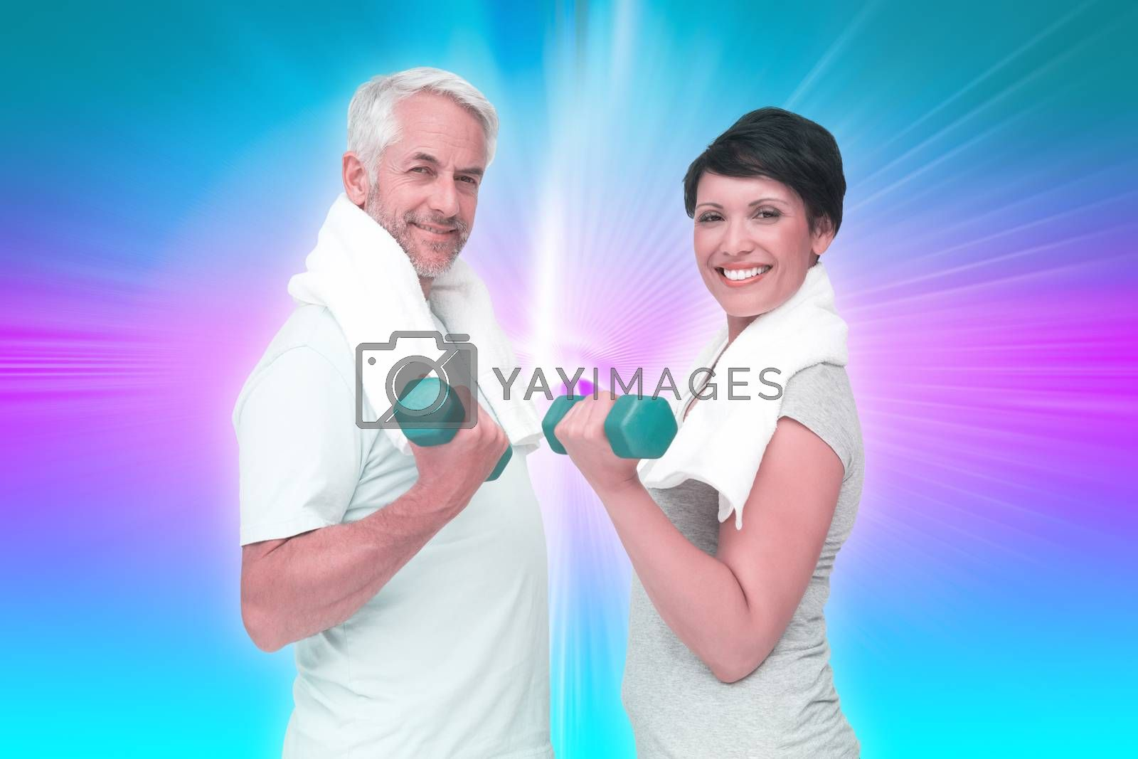 Fit mature couple exercising with dumbbells against abstract background