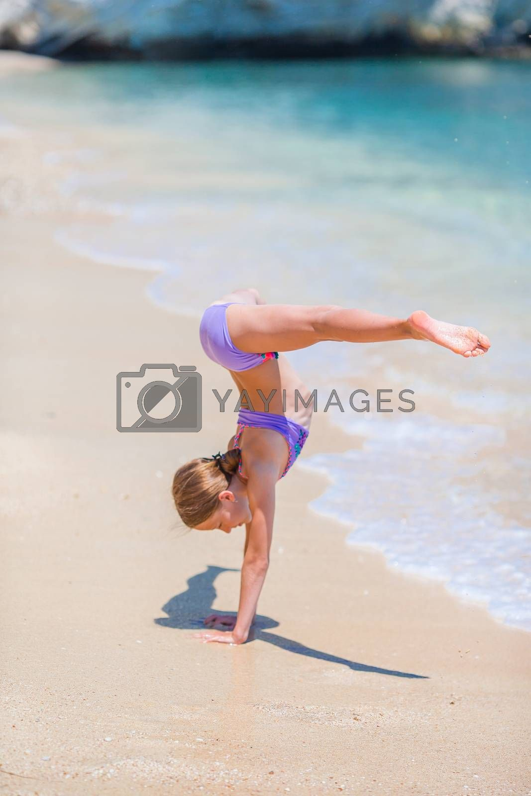 Little girl having fun at tropical beach during summer vacation playing at shallow water. Cute kid making sporty exercises on the seashore