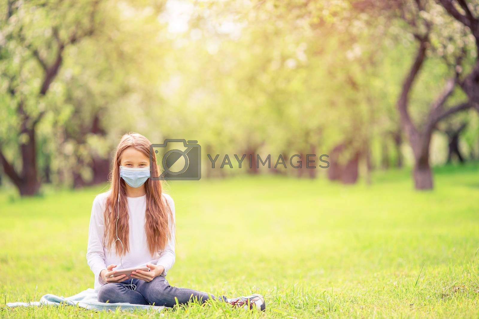 Little girl wearing a protective mask outdoors because of the coronavirus pandemic
