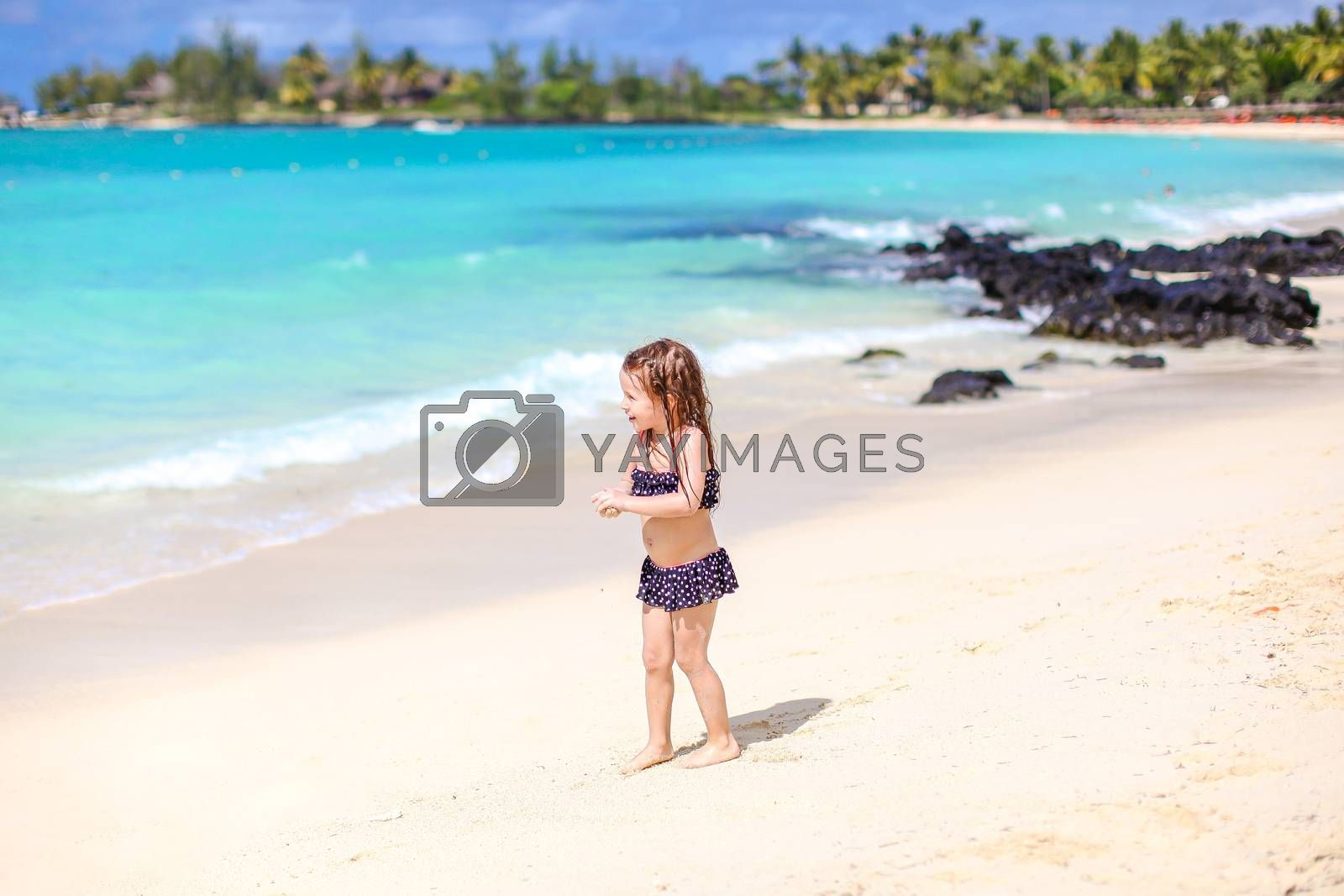 Little girl having fun at tropical beach during summer vacation on the seashore