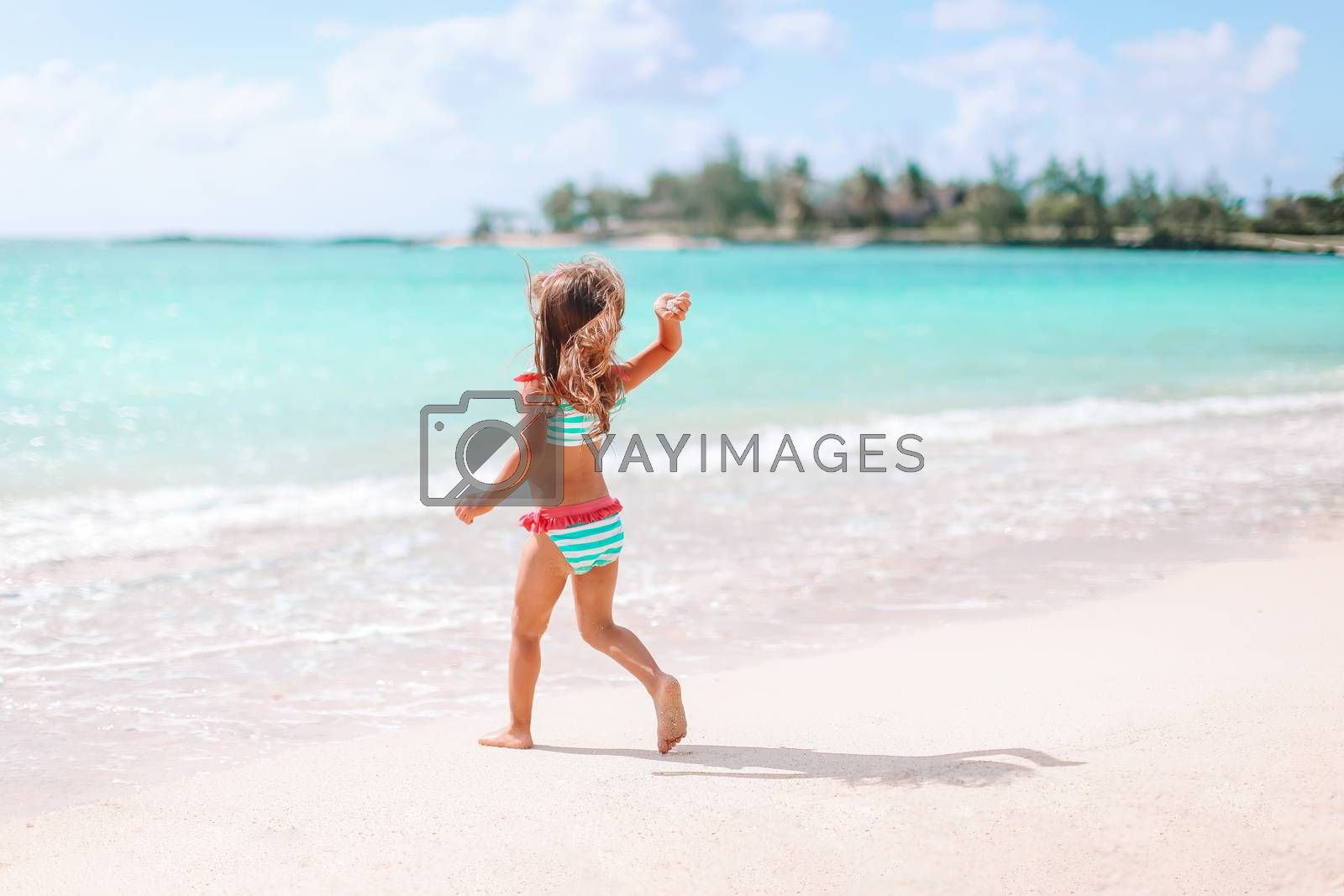 Little girl having fun at tropical beach during summer vacation playing at shallow water.