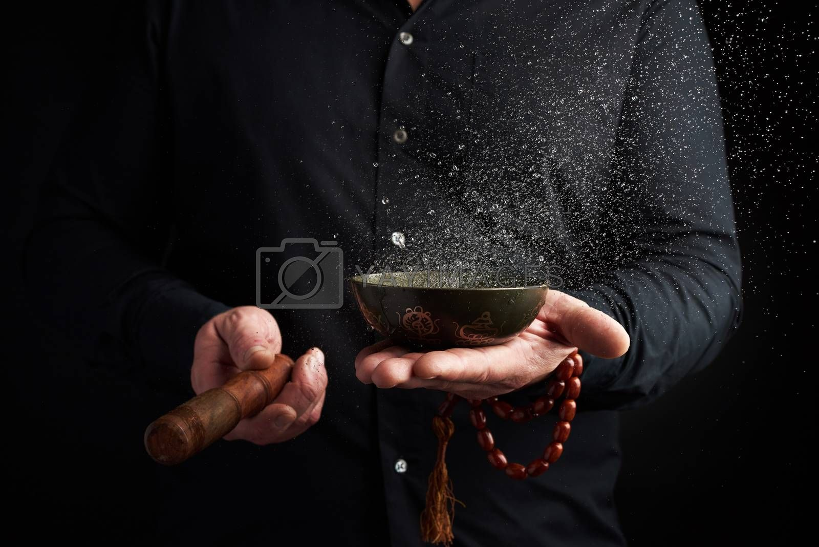 adult man in a black shirt rotates a wooden stick around a copper Tibetan bowl with water. ritual of meditation, prayers and immersion in a trance. Alternative treatment