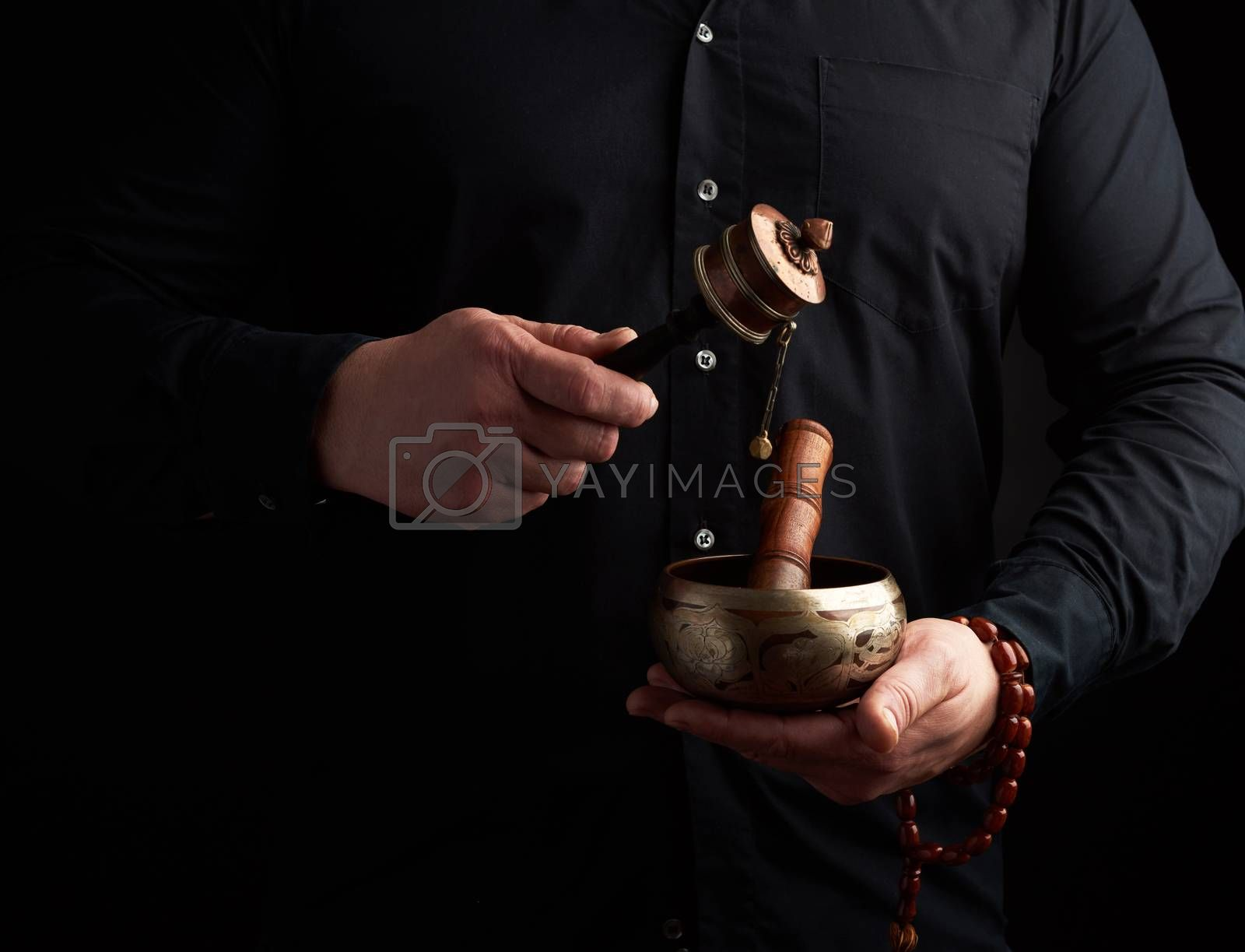 man in a black shirt holds a Tibetan brass singing bowl and a wooden stick and a prayer drum, a ritual of meditation, prayer and immersion in a trance. Alternative treatment