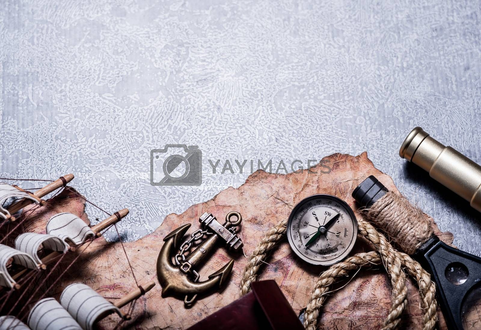 Columbus Day. Pirates and treasure with vintage world map and discovery of old equipment. Exploration and investigation with copy space on dark background. by graphixchon