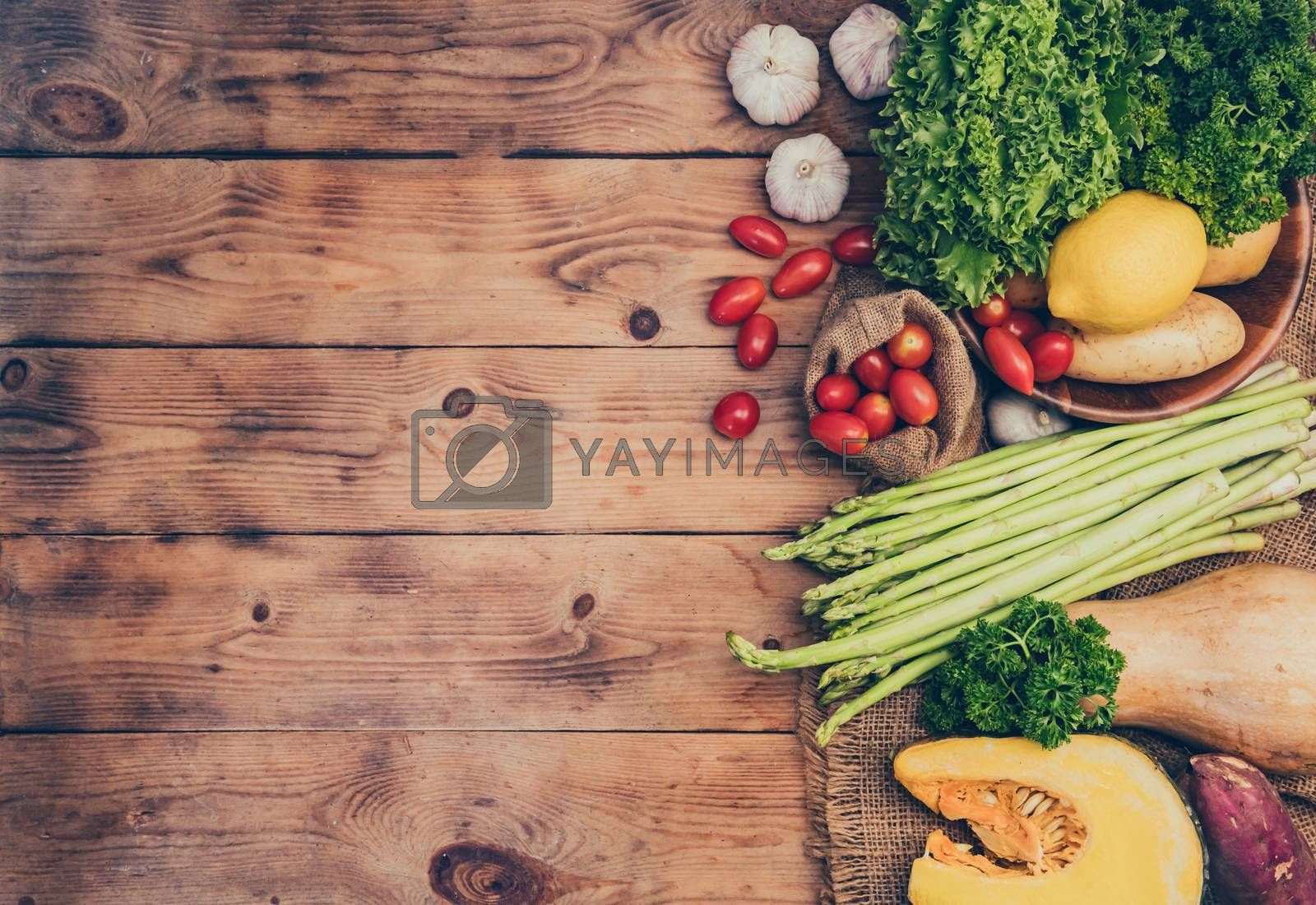 Fresh organic vegetables on wood backgroundfor cooking salad. Diet and healthy food. Fall harvest cornucopia in autumn season. by graphixchon