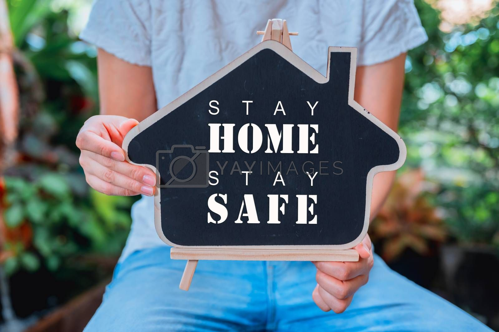 People holding wooden house with text.Stay home Stay safe concept. Self-quarantine and Social distancing. New normal and life after COVID. by graphixchon