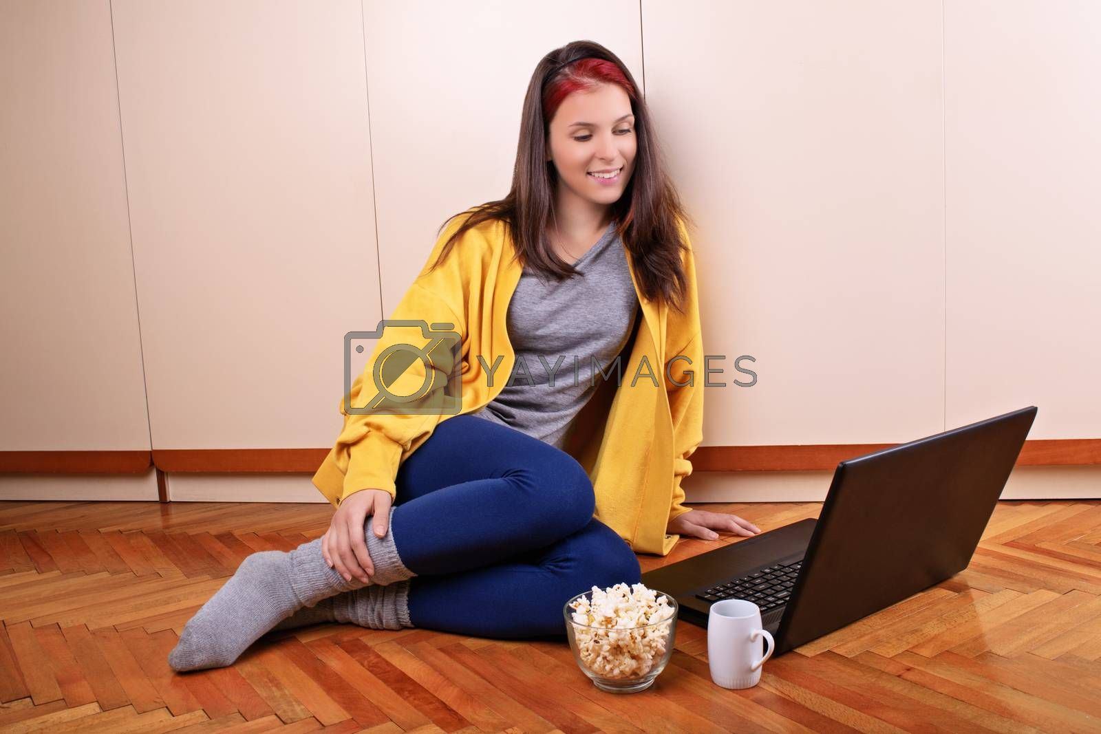 Beautiful smiling young girl in casual clothes sitting on the floor of her bedroom, ready to watch a movie on her laptop with a bowl of popcorn and a cup of coffee or tea. Leisure concept.