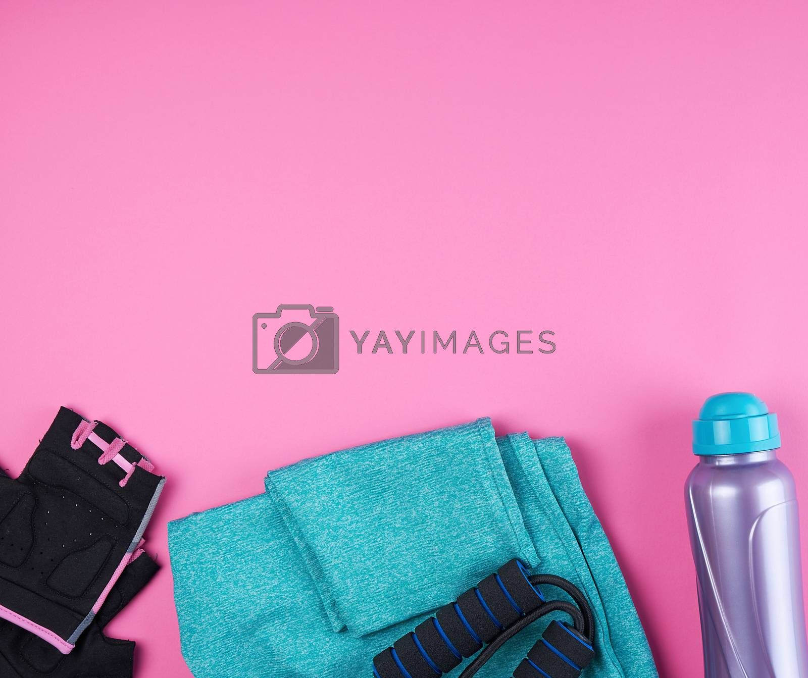 pink women's sneakers, bottle of water, gloves and a jump rope for sports on a pink background, top view, copy space
