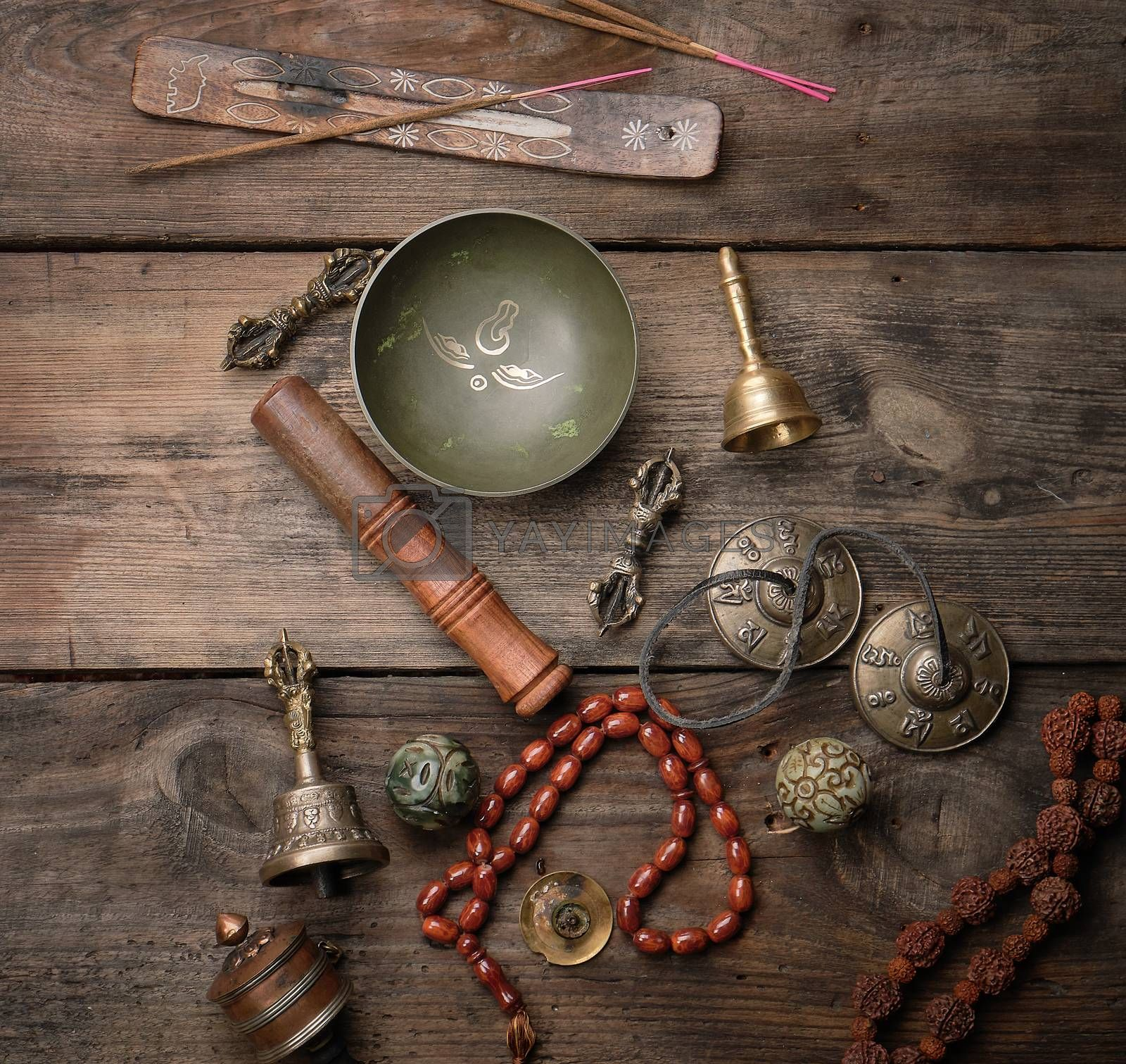 Copper singing bowl, prayer beads, prayer drum and other Tibetan religious objects for meditation and alternative medicine on a brown wooden background