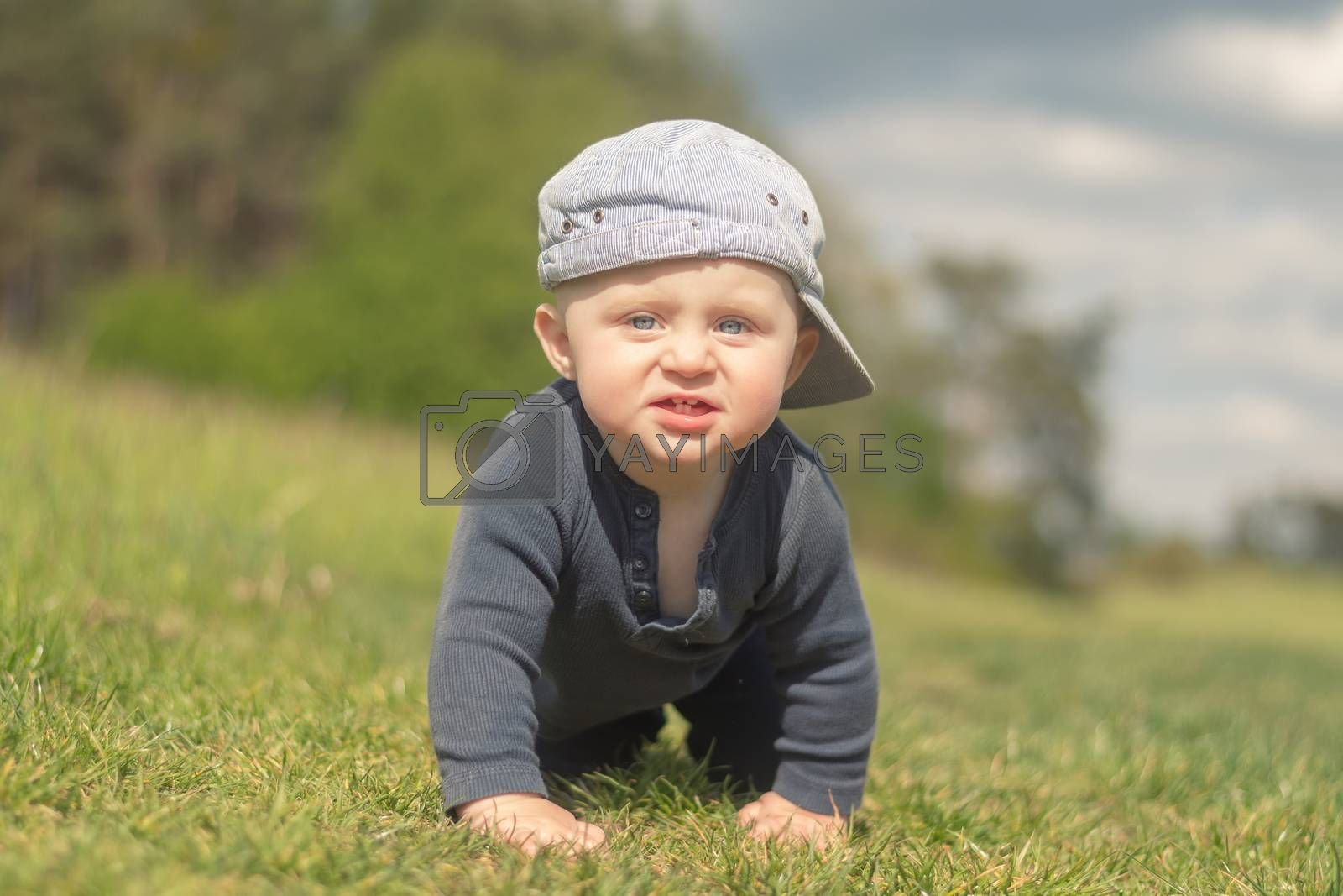 92/5000 An 11-month-old infant in a peaked cap climbs the lawn. Looking into the camera. Blurred background.