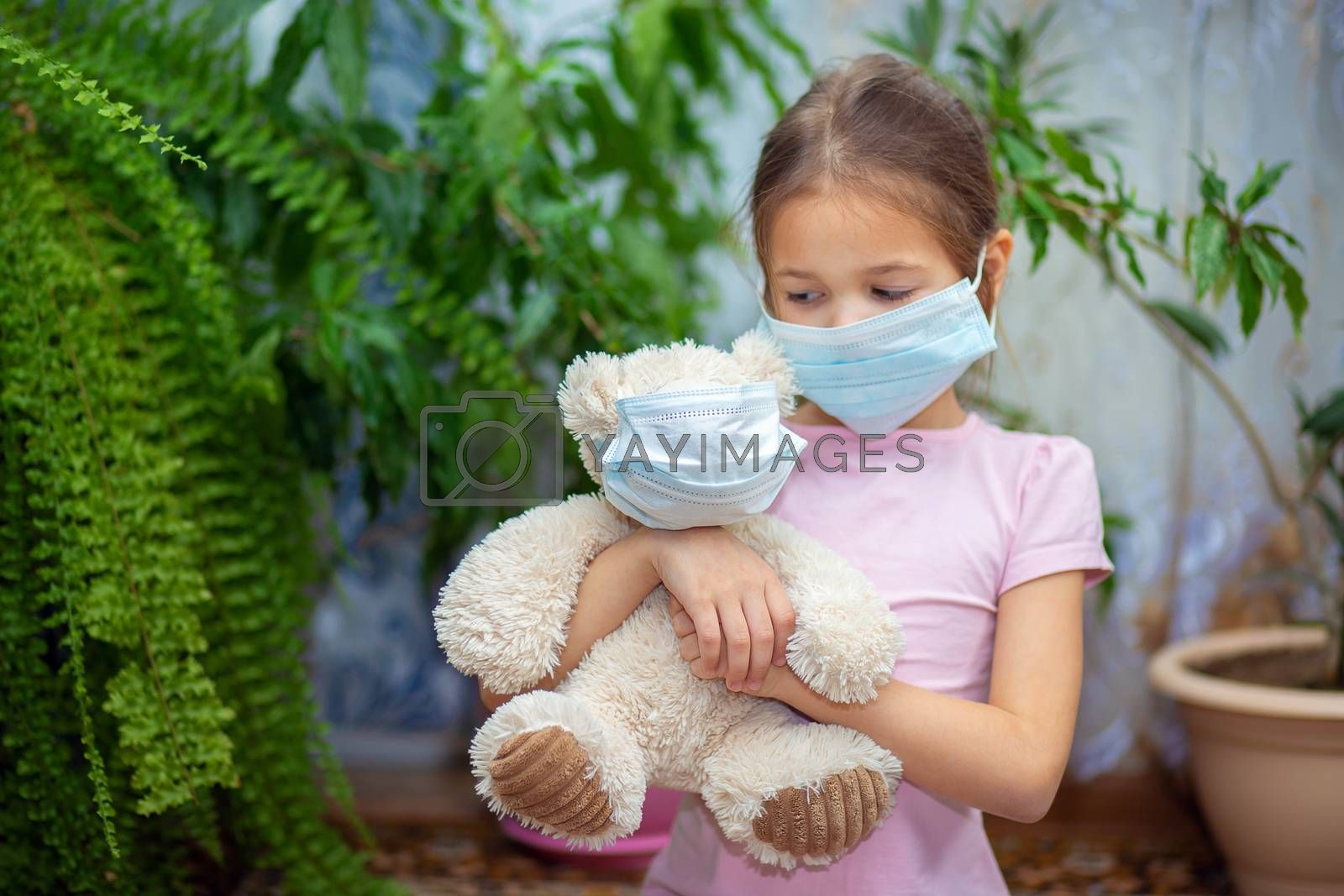 The girl put on a medical mask on herself and on her teddy bear. Quarantine