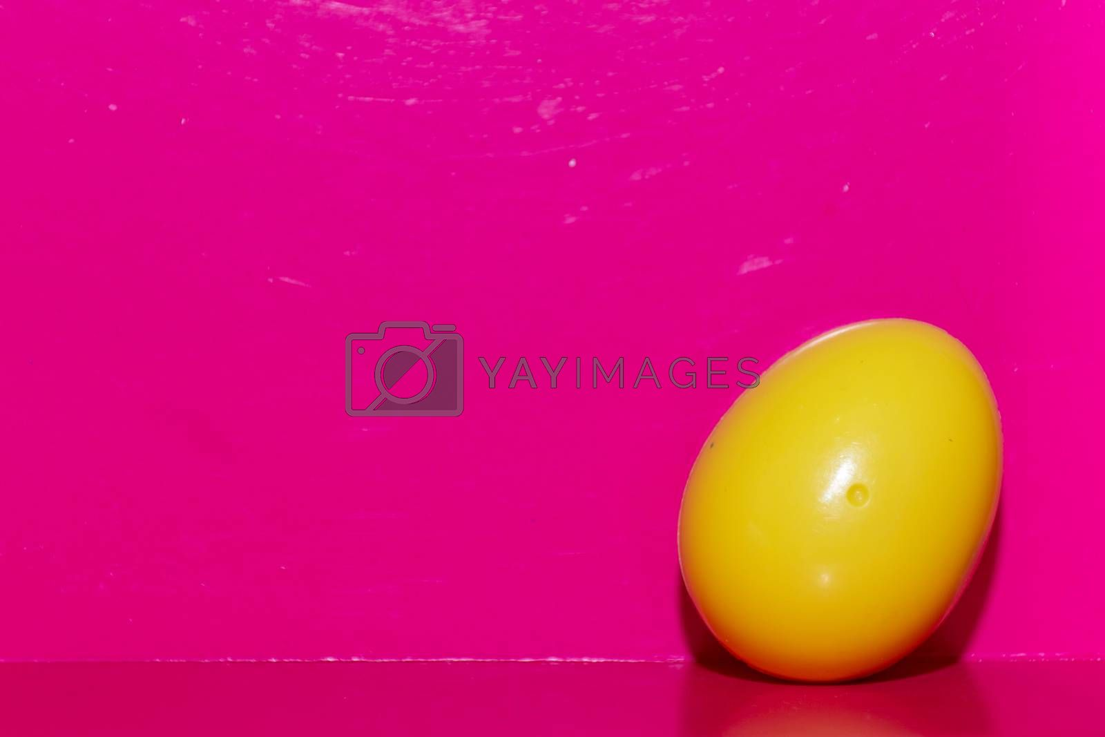Yellow plastic egg in bottom right corner of a deep bright pink background. Open space. Concept.