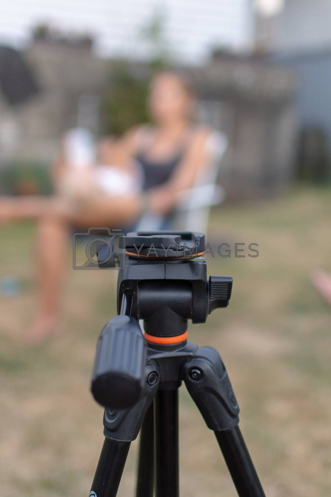 An empty black tripod looking towards a blurred women and child outdoors for a photography shoot. Conceptual.