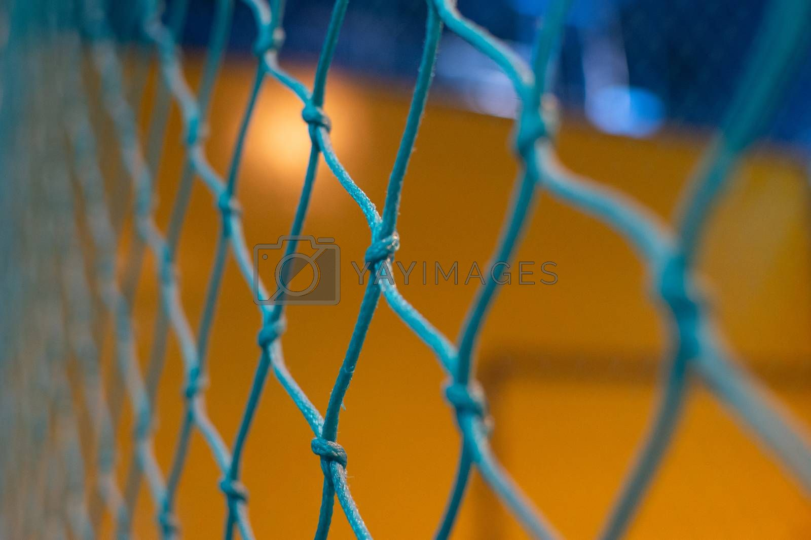 Looing through a blue net to a yellow and blue background blurred out. Games, sports, goals, or concepts.