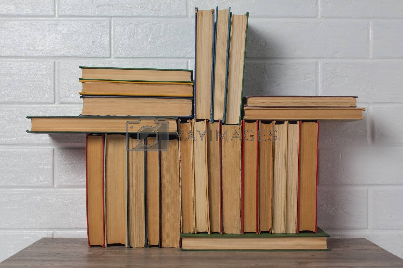 A stack of old books. Bookstore, library, bookshelf. Vintage, retro, antique. Study, education, school, University. Literature, history, science. Books against a white brick wall.