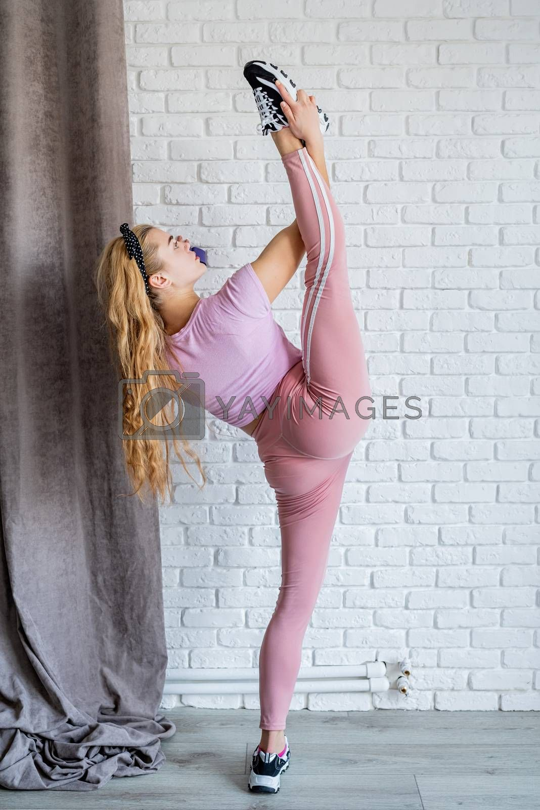 Fitness, sport, training and lifestyle concept. Athletic woman wearing pink sportswear stretching at home