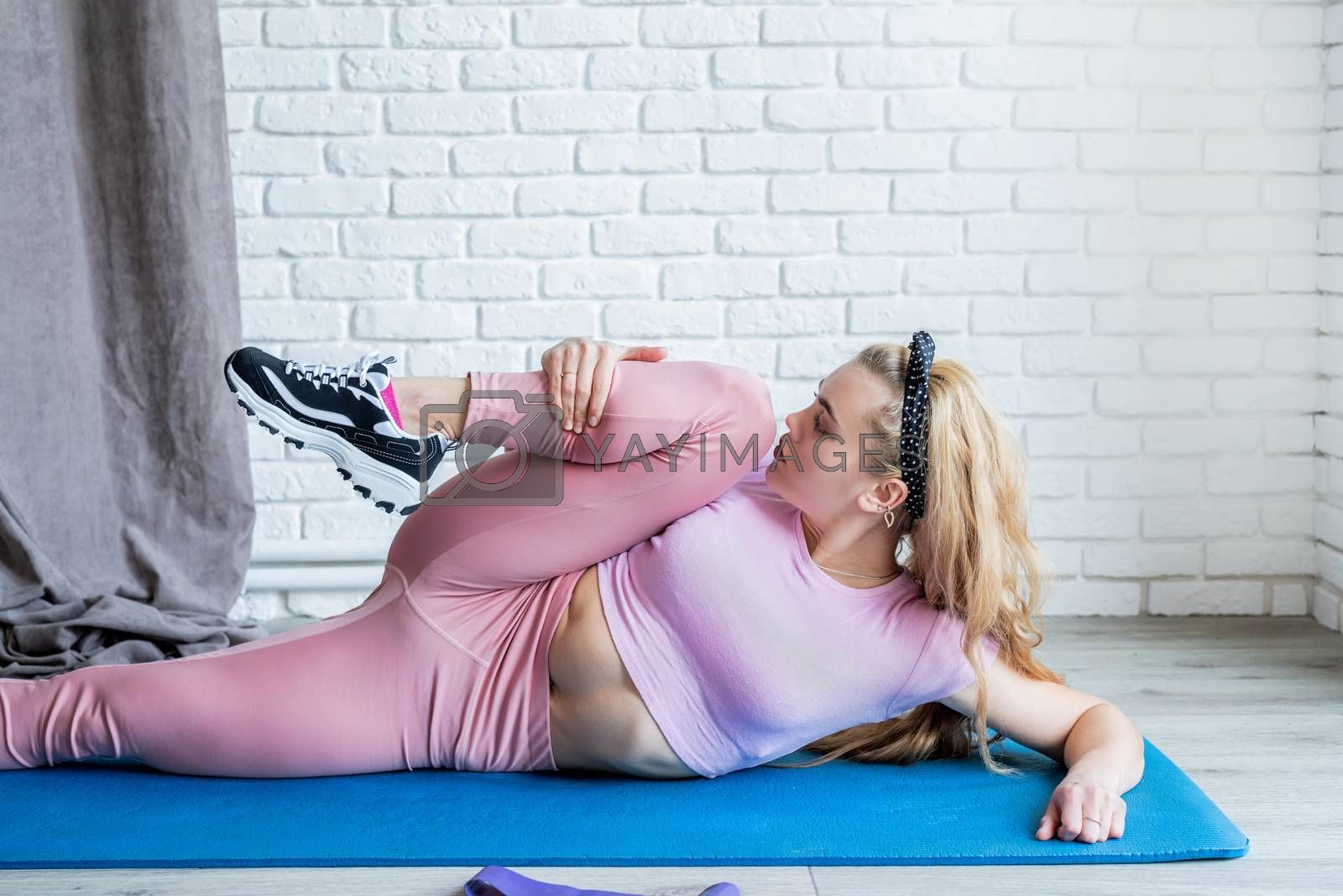 Fitness, sport, training and lifestyle concept. Staying home. Sportive caucasian woman doing exercises at the training mat at home
