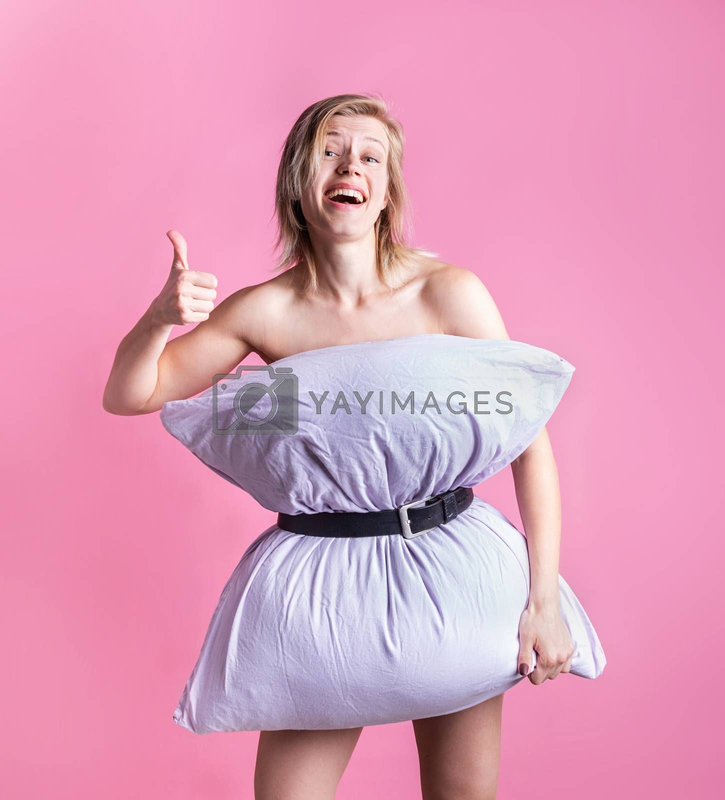 Coronavirus quarantine. Crazy quarantine. Young blond woman dressed in pillow laughing showing thumbs up on pink background. Pillow challenge outbreak