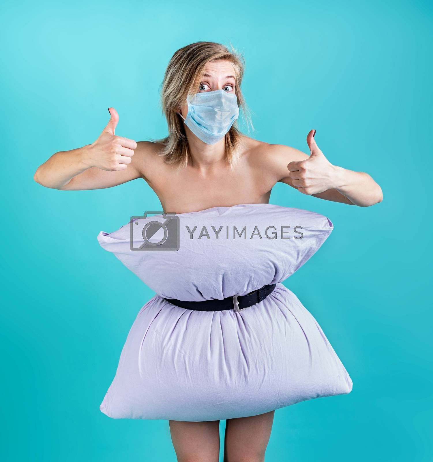 Coronavirus quarantine. Crazy quarantine. Blond woman in pillowdress wearing a mask showing thumbs up isolated on blue background. Pillow challenge outbreak
