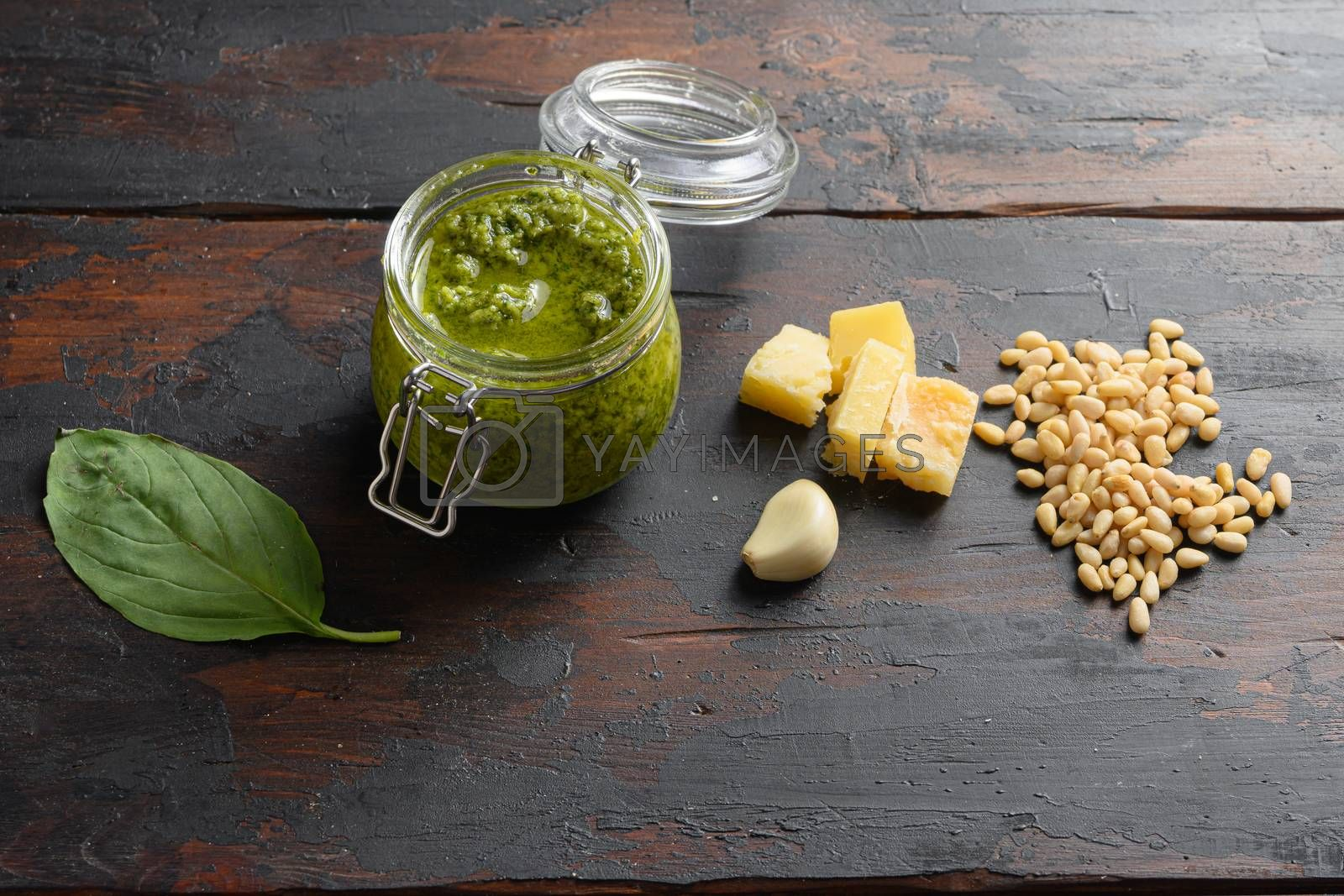 home made Pesto alla Genovese in glass jar with ingredients parmesan basil pine nuts. on dark wood table planks vintage side view.