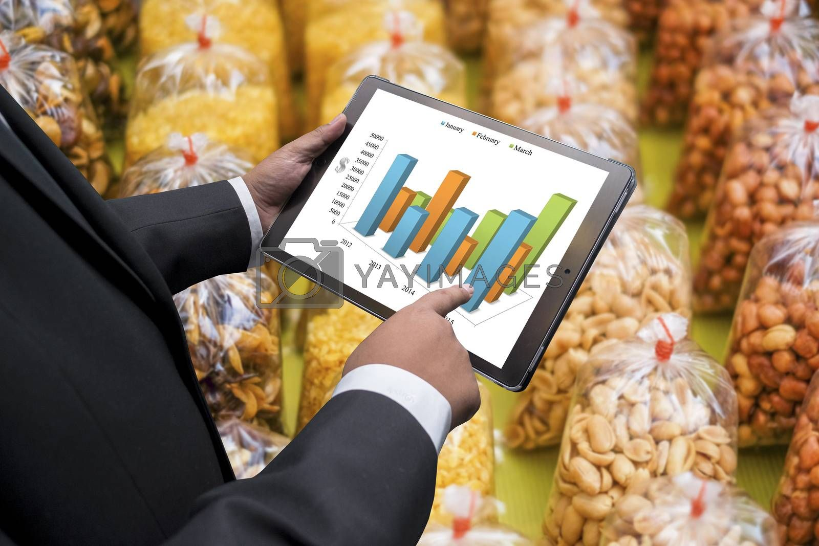 Business man doing agricultural business  on the screen of a touch-pad
