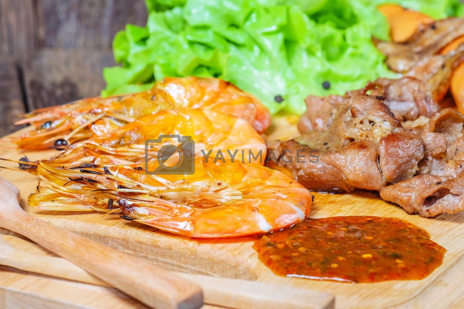 Grilled meat and shrimps with vegetables, barbecue grill food on wood background