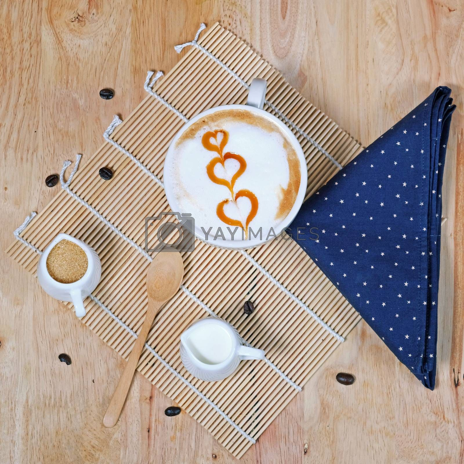 Capucino art coffee on wooden texture table by Surasak