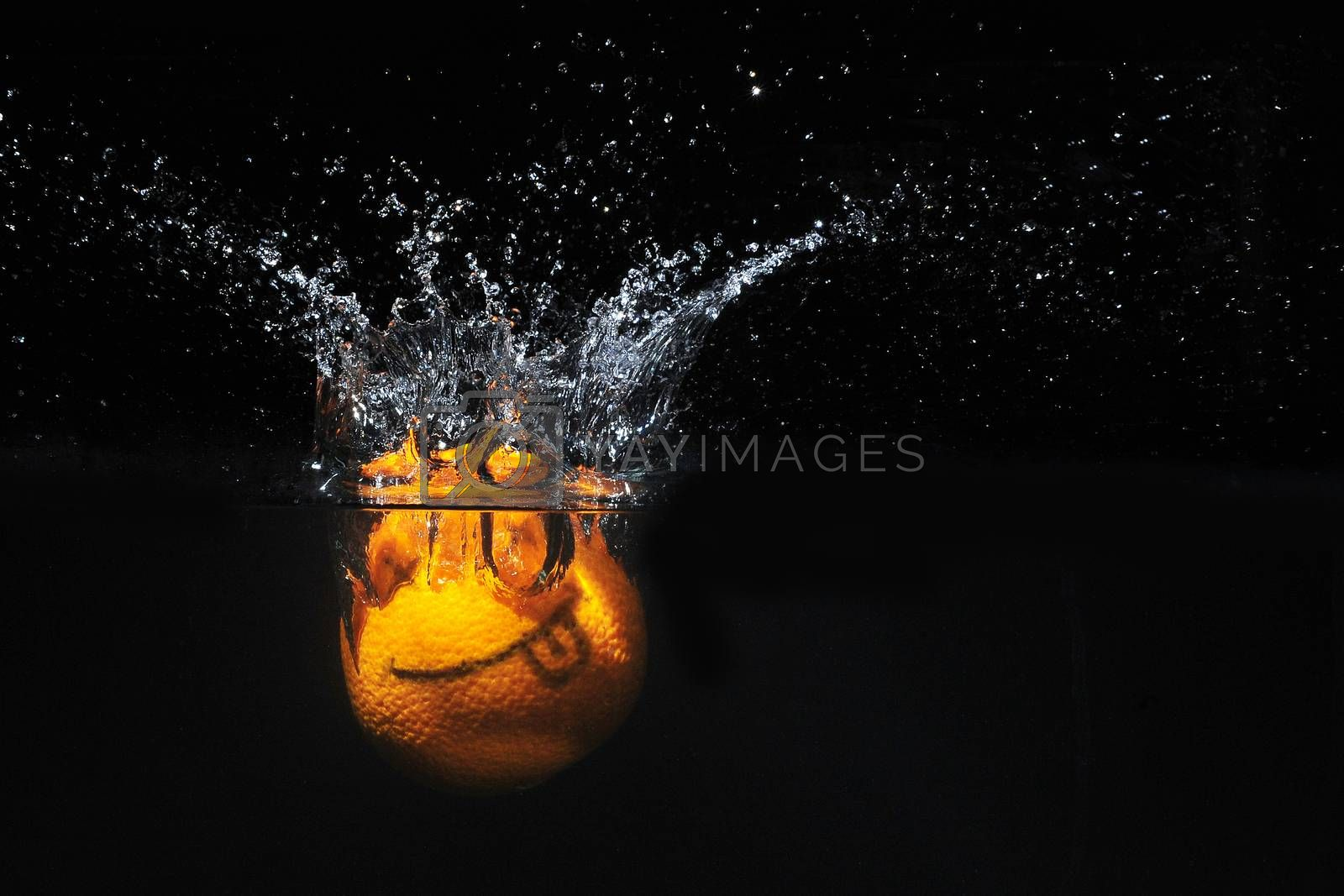Smile orange with splashes of water on a black background by Surasak