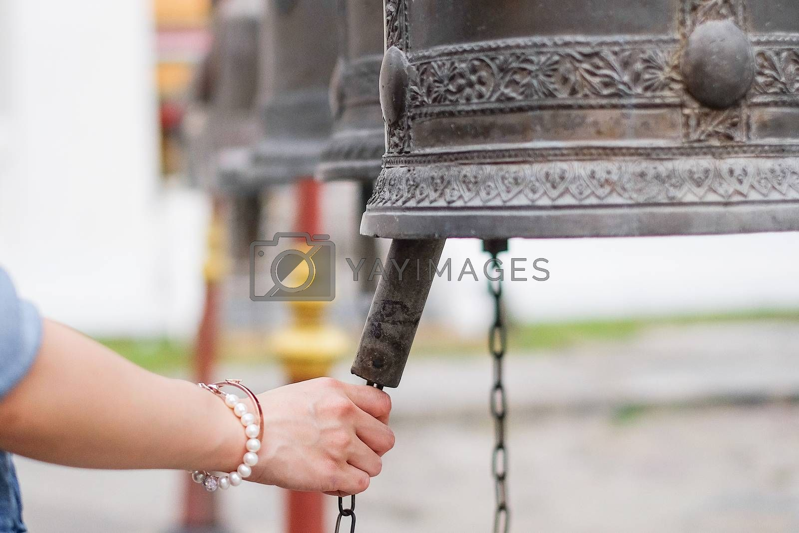 Woman ringing a bell in a Buddhist temple in Thailand by Surasak