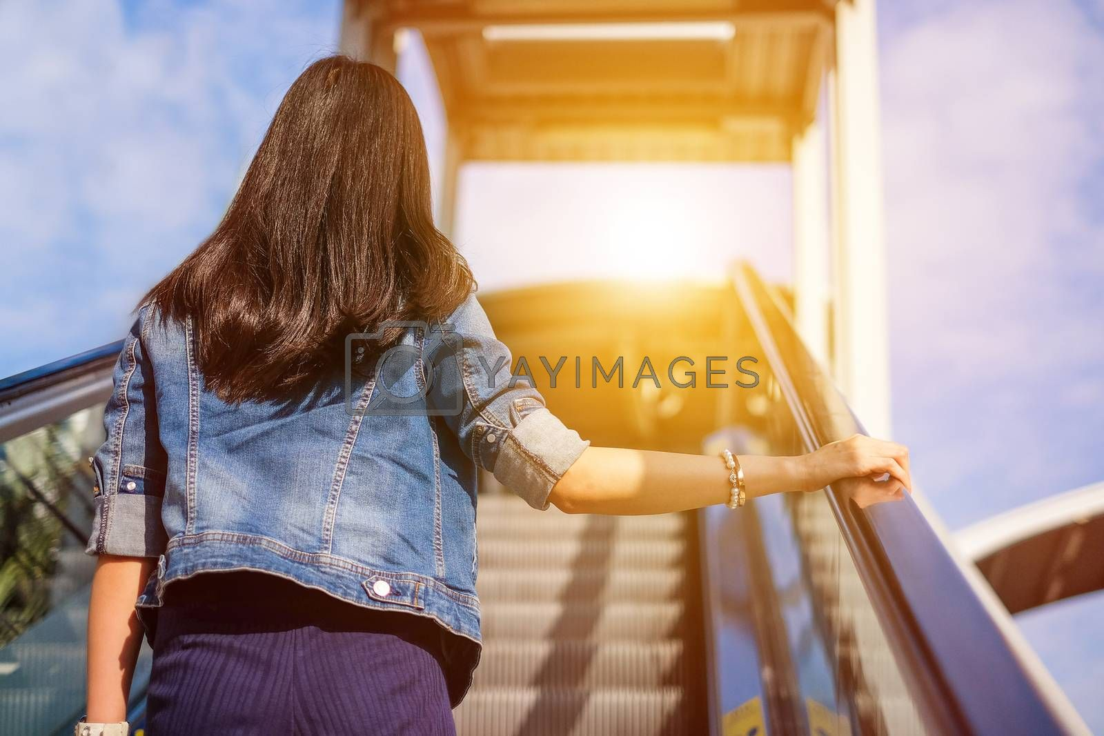 Young woman walking up stairs to reach her destination by Surasak