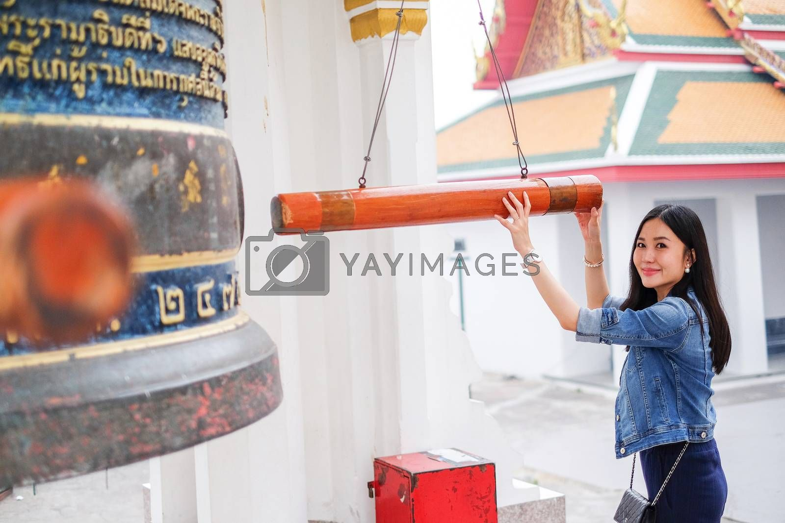 Woman ringing a bell in a Buddhist temple in Thailand