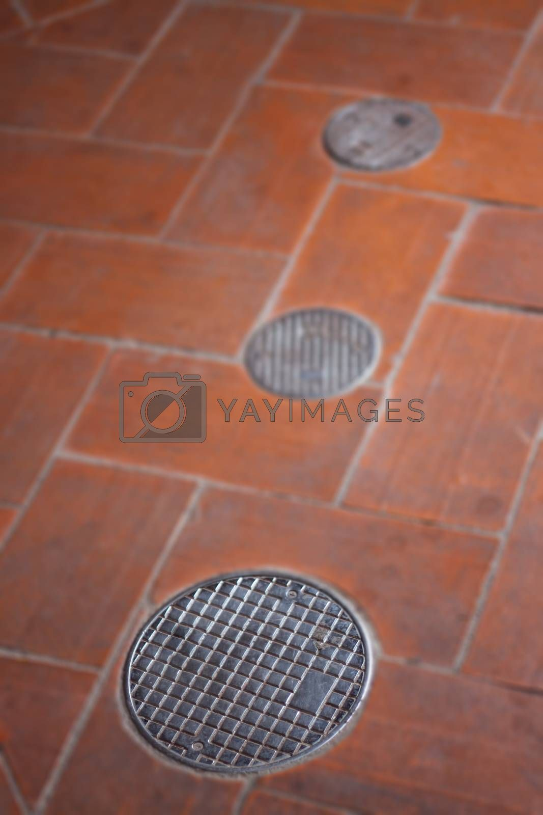 Small round manhole cover on the footpath, stock photo