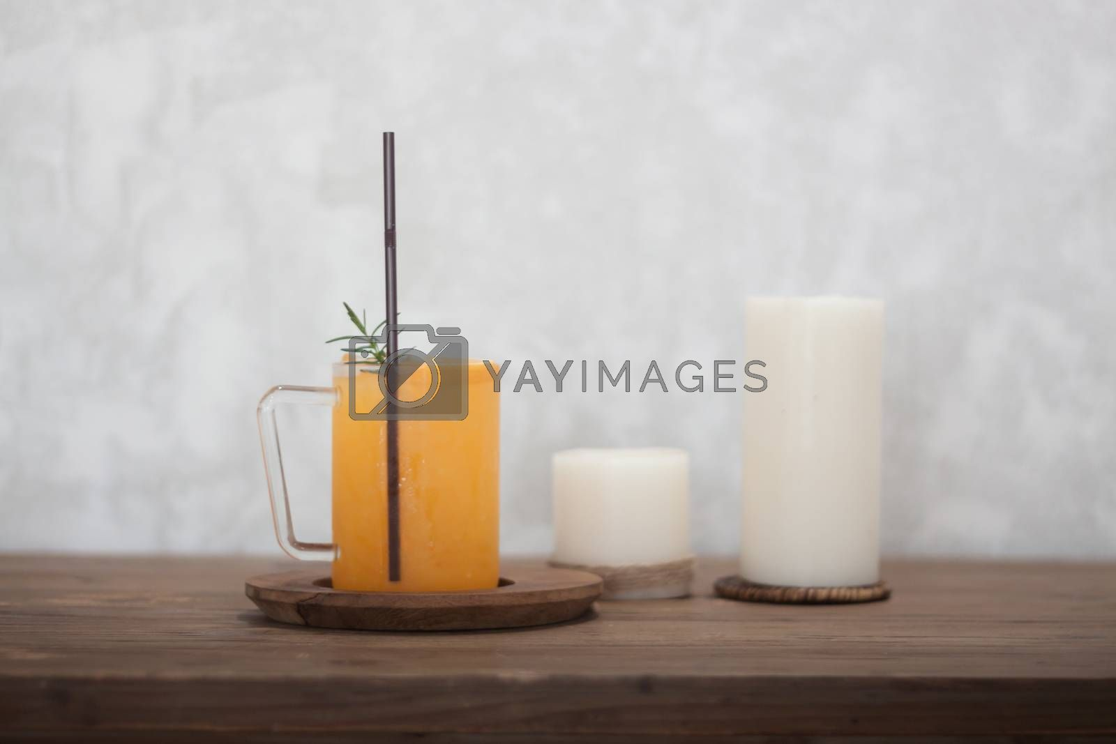 Glass of orange juice on wooden table by punsayaporn