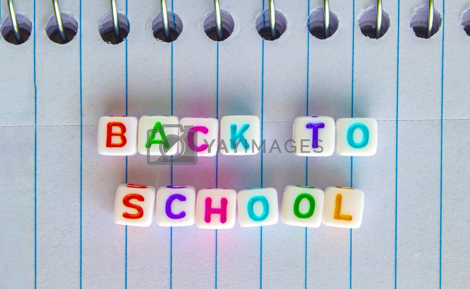 Back to School, message in colorful text on white cubes on a notebook
