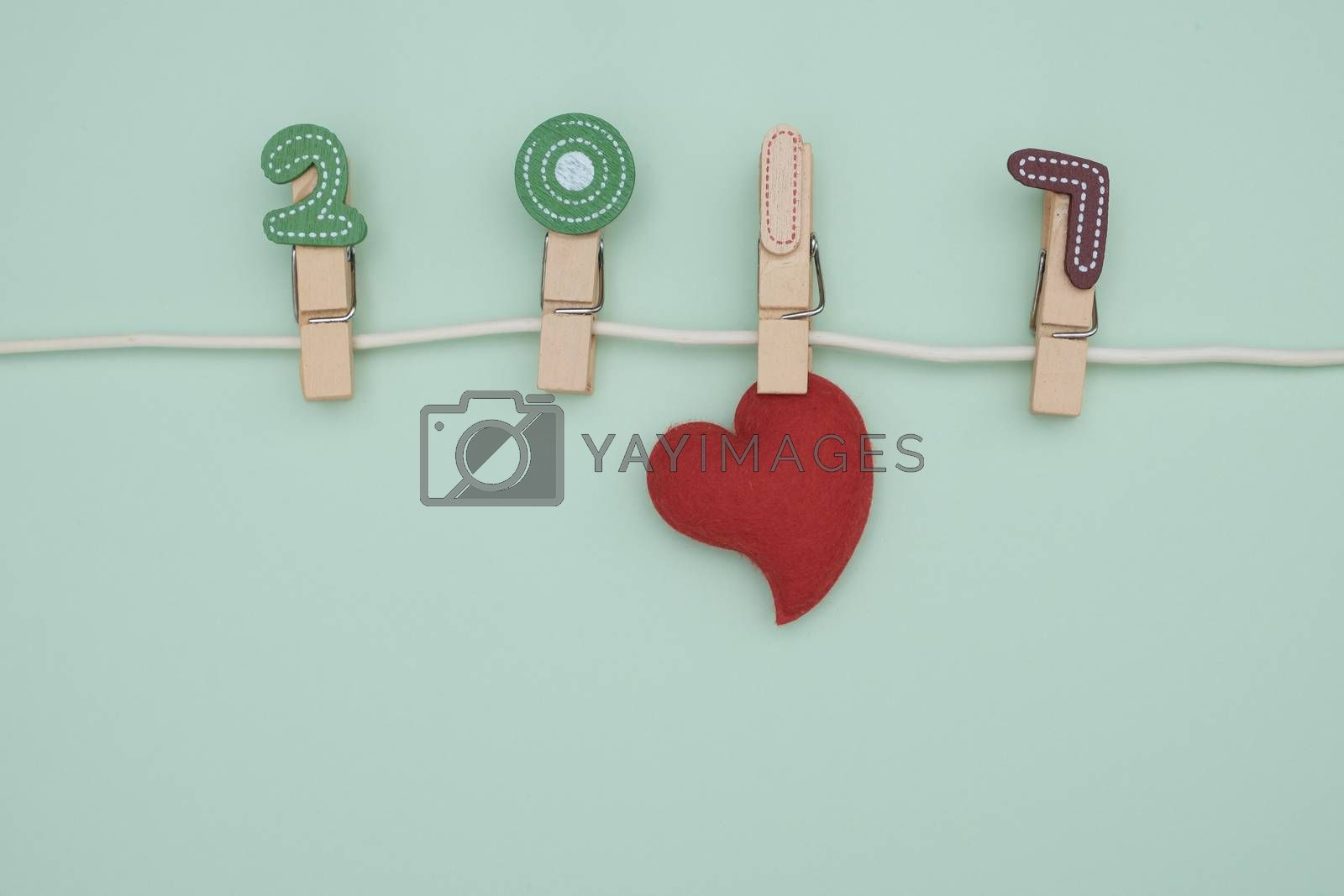 Red pillow heart hanging on the clothesline. On blue background. Valentine concept